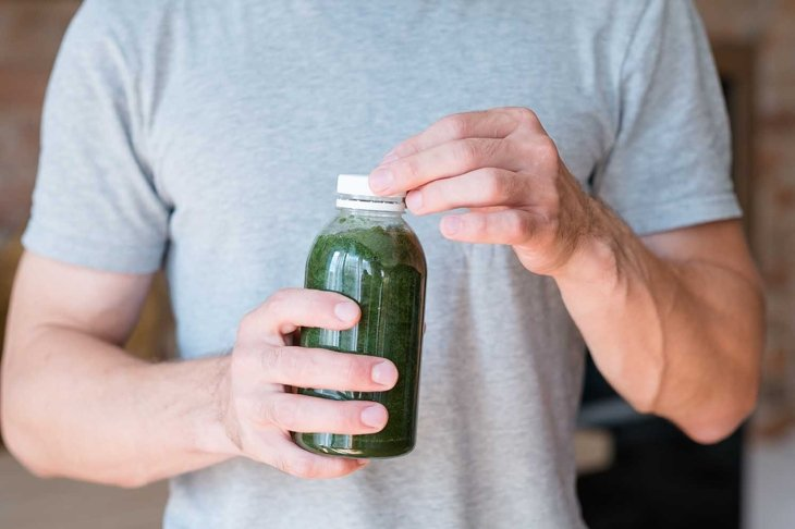 man holding bottle with green smoothie. detox drink and healthy lifestyle