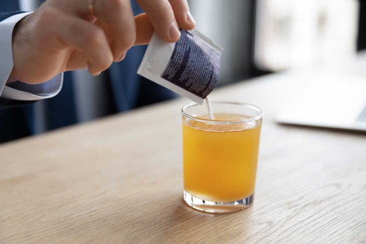 Close up young businessman pouring soluble anti-influenza orange powder with citrus taste in glass of water, feeling first grippe illness symptoms at workplace or relieving headache with painkiller.