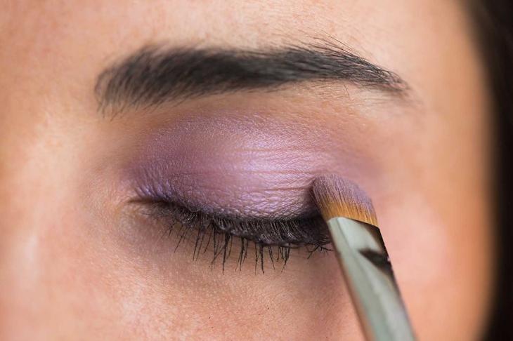 Woman getting purple eye shadow applied