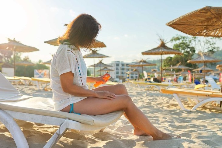 Mature woman sitting on sun lounger on sandy beach applying sunscreen to her leg. Health care, beauty, relaxation, sea holidays