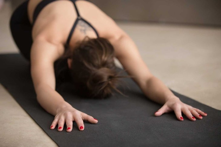 Young attractive woman practicing yoga, stretching in Child exercise, Balasana pose, working out, wearing black sportswear, urban style grey studio floor, close up, focus on fingers