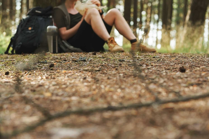 Woman hiker sitting in forest. Camera focus on the ground.