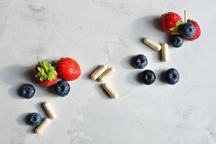 Keto Fresh Organic Strawberry and Blackberry Next to Enzyme Supplement Pill for digestive health safe on a ketogenic diet