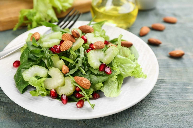 Delicious fresh celery salad on light blue wooden table, closeup