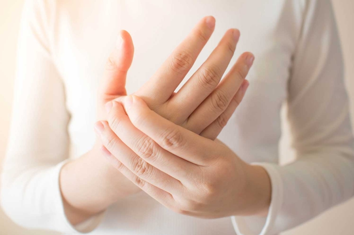 Young female in white t-shirt suffering from pain in hands and massaging her painful hands. Causes of hurt include carpal tunnel syndrome, fractures, arthritis or trigger finger. Health care concept.