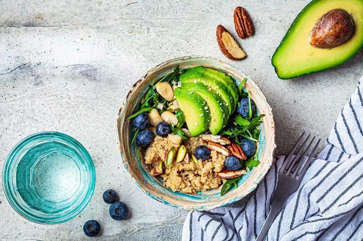 Vegan quinoa salad with berries, avocado and nuts. Healthy vegan food.