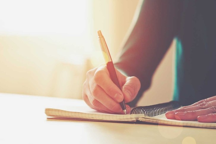 female hands with pen writing on notebook