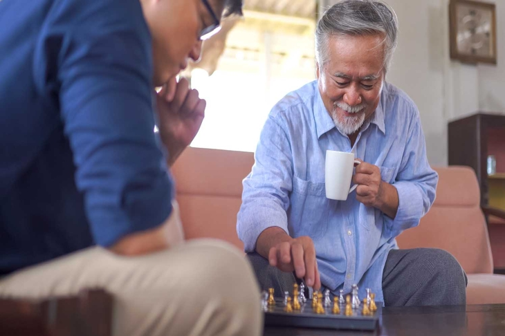 Asian Senior man playing chess with son at home