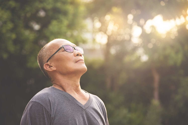 Happy Asian senior male wear glasses relaxing and breathing fresh air at park with sunlight and copy space. Elderly male smiling standing over nature on holiday. Carefree, Lifestyle, Wellness.