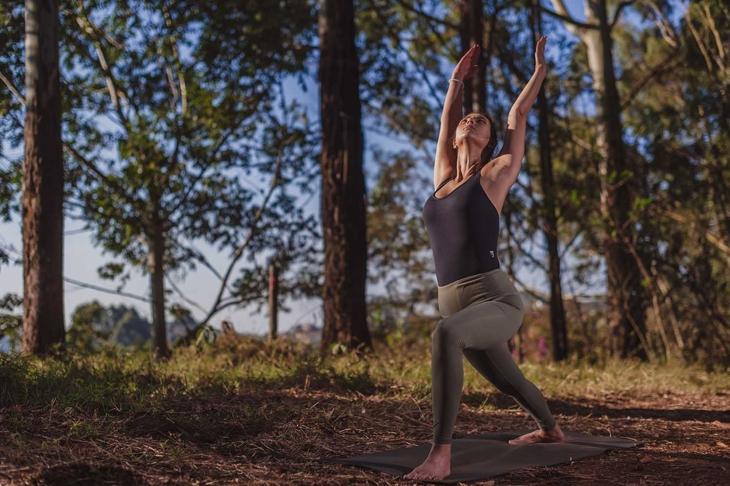 Beautiful brunette yoga woman teacher practicing deep breathing in the wild nature