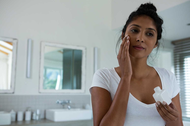 Close up of young woman applying lotion in bathroom at home