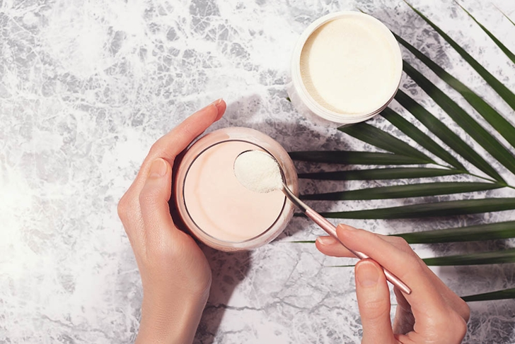 Woman pour collagen powder or protein in morning smoothie or yogurt. Natural beauty and health supplement. Healthy lifestyle. Flatlay, top view. Copy space.