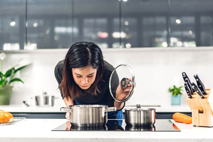 Young asian woman standing near stove and cooking.Happy woman looking and smelling tasting fresh delicious from soup in a pot with steam at white interior kitchen