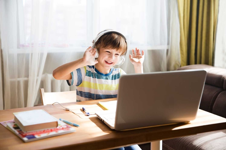 child boy in headphones is using a laptop and study online with video call teacher at home. homeschooling, distant learning