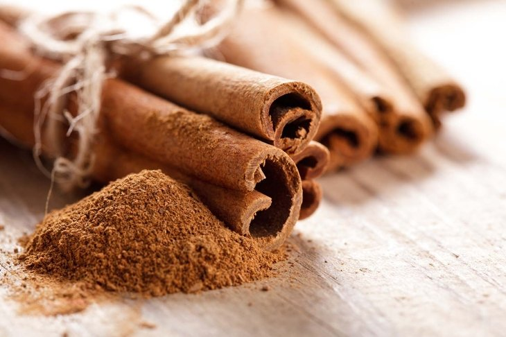 Cinnamon sticks and meal close up on wooden table