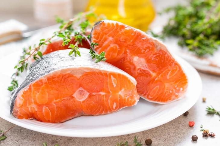 Fresh raw salmon fish steaks on white kitchen background