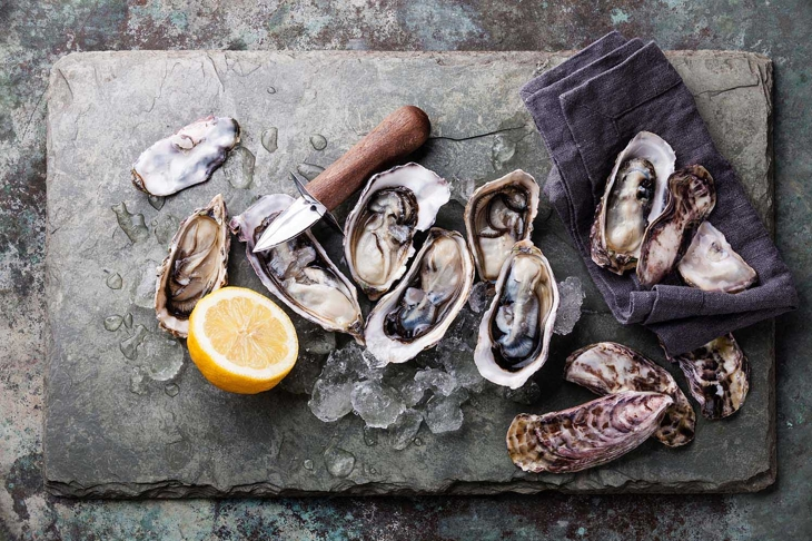 Oysters on stone plate with ice and lemon