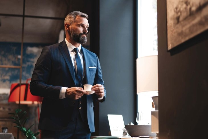 Enjoying fresh coffee while working. Confident man in smart casual wear holding coffee cup at his working place in office