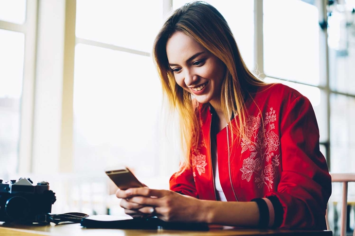 Happy young professional photographer installing new photo application on modern telephone device.Positive female blogger uploading pictures and videos on own web page via high speed internet