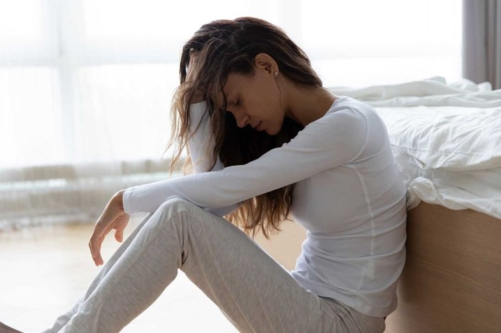 Unhappy woman touching hair, sitting on floor at home, thinking about problems, upset girl feeling lonely and sad, psychological and mental troubles, suffering from bad relationship or break up