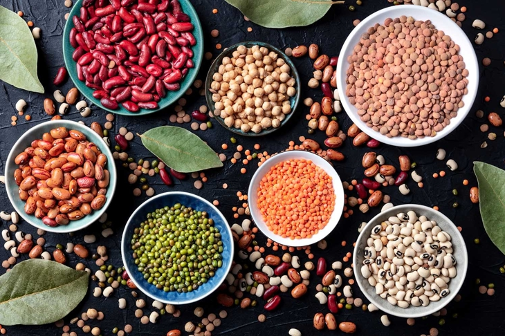 Legumes assortment, shot from the top on a black background. Lentils, soybeans, chickpeas, red kidney beans, a vatiety of pulses