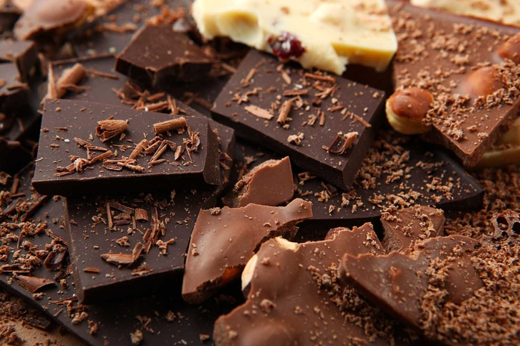 Chocolate products of different types on a colored background close-up with a place for text