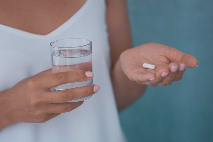 Woman arm holding small round med and glass of water before taking medication, shallow depth of field, focus on medicine