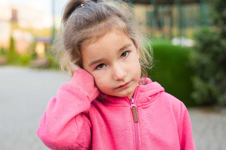 A little girl in a pink hoodie with a sad and tearful face is holding her ear. Ear pain, otitis media, swelling of the cheek, gums, toothache, children's surgery, otolaryngology. Children's medicine
