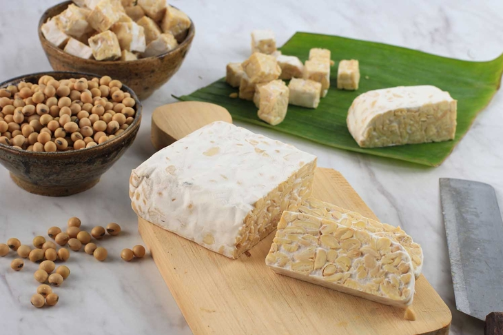 Raw Tempeh or Tempe. Tempeh Slices on Wooden Background, Cut by Asian Female Chef. Tempe Made From Fermented Soybeans. Copy Space for Text. Concept of Soy Product