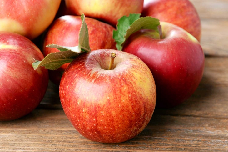 Ripe red apples on wooden background