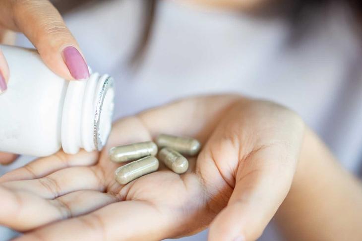 closeup woman hand taking herb medicine tablets