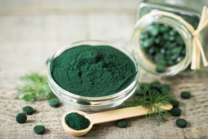 Spirulina powder and tablets in the bowl