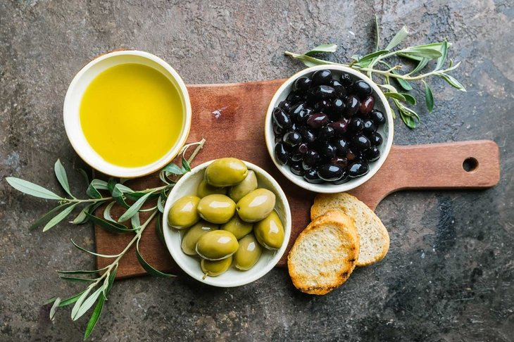 A set of Green and black olives and olive oil on a dark stone background, top view