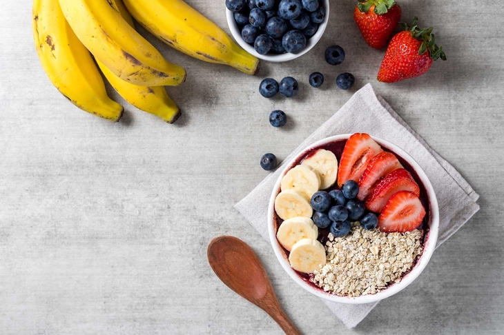 Brazilian frozen açai berry ice cream bowl with strawberries, bananas, blueberry and oatmeal flakes. with fruits on wooden background. Summer menu top view