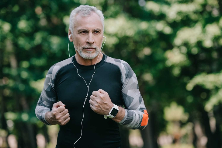 handsome mature sportsman listening music in earphones while running in park