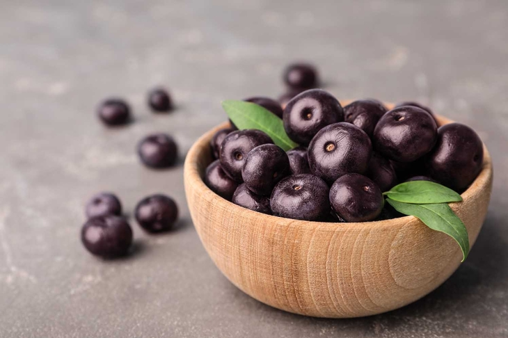 Bowl of fresh acai berries on grey stone table, closeup view. Space for text