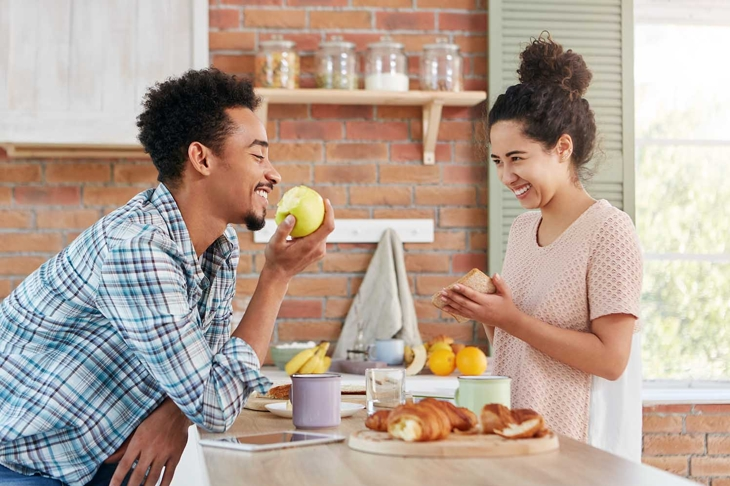 Newlyweds spend time together, speak pleasantly at kitchen, have good relationships. Smiling pretty brunette mixed race woman looks at husband who eats green apple and waits for delicious supper