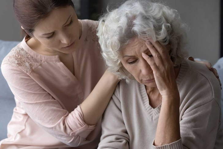 Close up loving daughter hugging, comforting frustrated mature mother, helping to overcome problems, unhappy senior female touching forehead, suffering from headache, feeling unwell