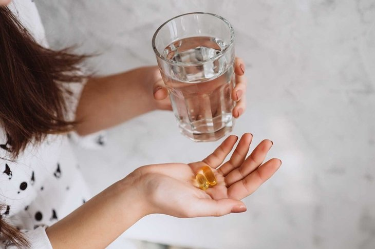 Diet. Nutrition. Girl's hands with pills with cod liver omega-3 oil and a glass of fresh water. The concept of a healthy diet and lifestyle. Vitamin D, E, fish oil capsules.