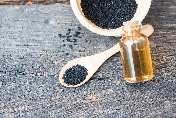Selective focus Nigella sativa (Black cumin) on wooden spoon and essential oil. Real oil from nigella looks like dark honey. Herbal medicine.