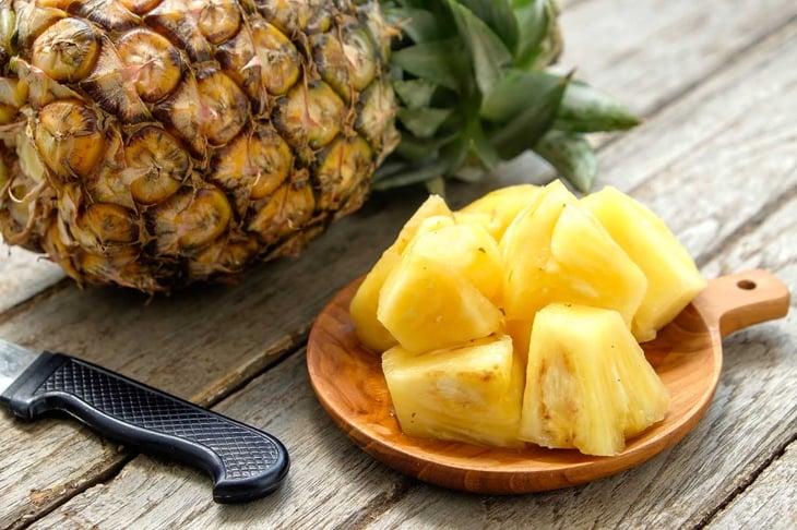 Pineapple fruit cut on wooden