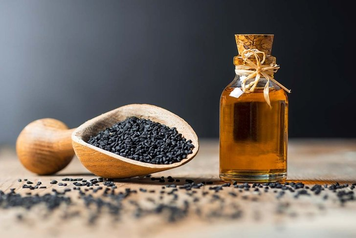 glass bottle of black cumin seeds essential oil , Nigella Sativa in spoon on wooden background. Organic herbal medicine for many diseases, black cumin