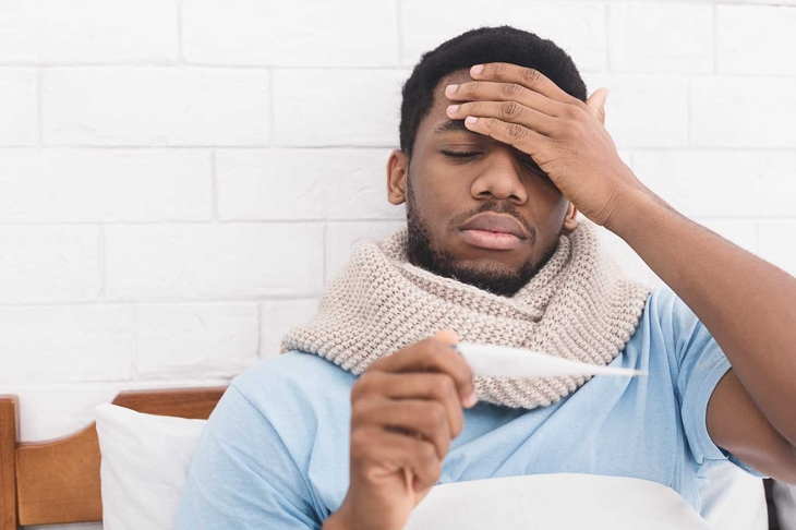 Sick african-american man having fever, measuring body temperature with thermometer, touching forehead in bed, copy space