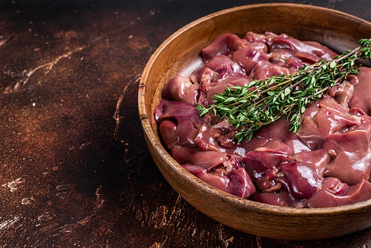 Raw chicken liver offals in a wooden plate. Dark background. Top view. Copy space