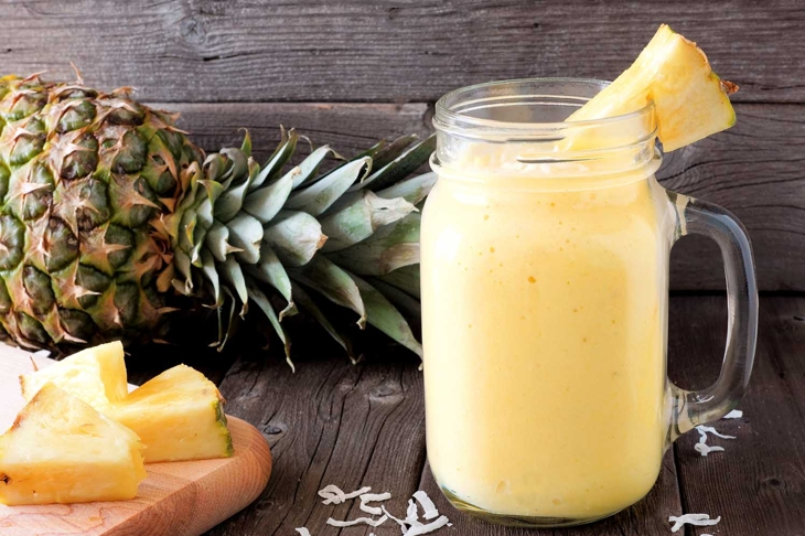 Tropical pineapple smoothie in a mason jar, scene against an old wood background