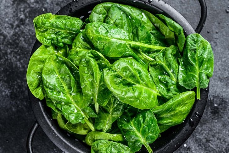 Young raw spinach in a colander. Black background. Top view