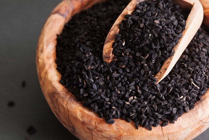 Black cumin or nigella sativa or kalonji seeds in bowl with spoon on black slate background, selective focus