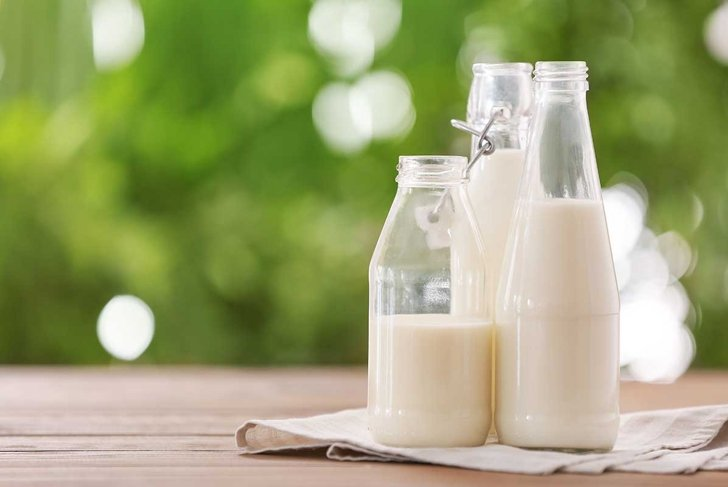 Bottles of fresh milk on table outdoors
