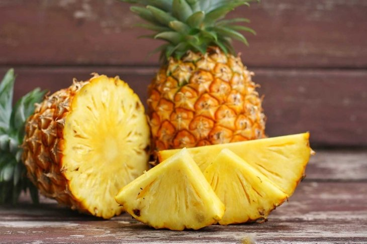Close up at Sliced and whole of Pineapple(Ananas comosus) on wooden table background.Sweet,sour and juicy taste.Have a lot of fiber,vitamins C and minerals.Food,Fruits or healthcare concept.
