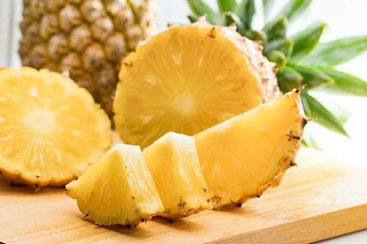 fresh pineapple fruit and pineapple slice on wooden table